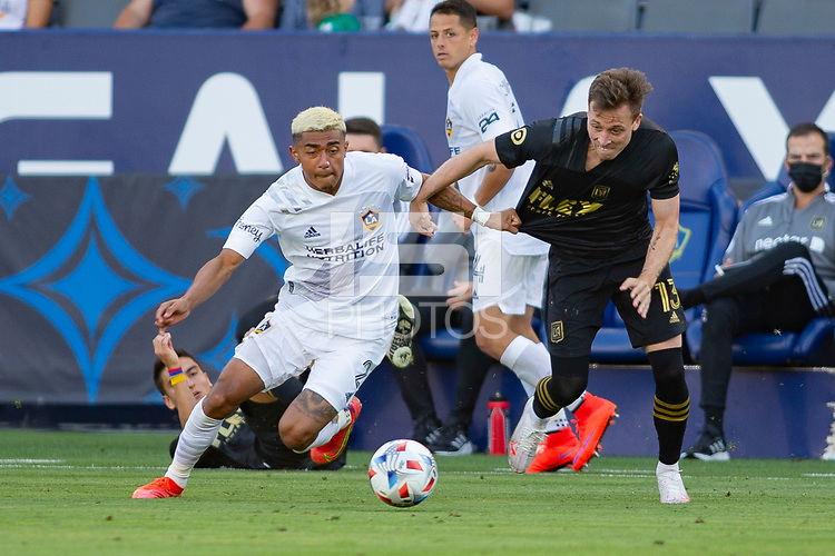 CARSON, CA - MAY 8: Julian Araujo #2 of the Los Angeles Galaxy battles with Corey Baird #13 of LAFC during a game between Los Angeles FC and Los Angeles Galaxy at Dignity Health Sports Park on May 8, 2021 in Carson, California.