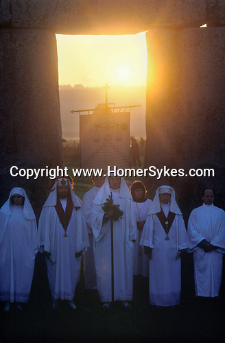 Druids celebrate the summer solstice at Stonehenge Wiltshire June 21st dawn sunrise. over the Heel Stone. 1970s.