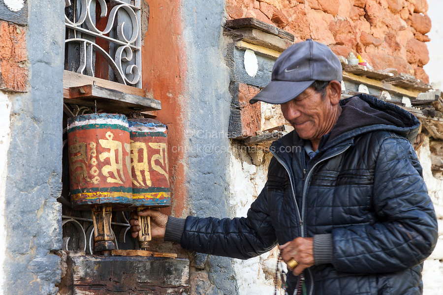 Bumthang, Bhutan.  Man Spinning Prayer Wheels at Jambey Lhakhang Temple and Monastery, near Jakar.