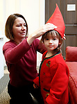 """Washington, CT- 29 December 2013-122913CM15  CL ONLY PLEASE----  Cara Abraham, of Washington helps her daughter, Darya, 2, into costume before the start of a miniature procession of Sankta Lucia, inside the Gunn Memorial Library in Washington on Sunday.  Darya portrayed """"Tomte"""" in the processional.  Christopher Massa Republican-American"""