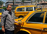"Gaza.June.13.2008.A Palestinian taxi driver Ahmad  Masri fills his vehicle with sun flower cooking oil instead of the usual fuel in the Falasten public square on June, 13, 2008 in Gaza City, Gaza Strip. Masri said he and many other Palestinian taxi drivers resorted to using cooking oil instead of the fuel in an attempt to keep them working . "" Photo by Fady Adwan/propaimages"""