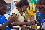 A woman holds a brochure about HIV/AIDS and sex while listening to a behavior change communication session about HIV/AIDS prevention and transmission.  The session is presented by the Society for Family Health (SFH), Nigeria's largest indigenous non-governmental organization (NGO) and partner of the international public health NGO, Population Services International (PSI).