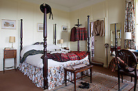 Kilts woven in the traditional Munro tartan spread over a four-poster bed