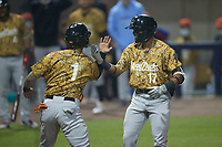 Keyber Rodriguez (17) of the Down East Wood Ducks slaps hands with teammate Cody Freeman after hitting a 2-run home run against the Kannapolis Cannon Ballers at Atrium Health Ballpark on May 8, 2021 in Kannapolis, North Carolina. (Brian Westerholt/Four Seam Images)