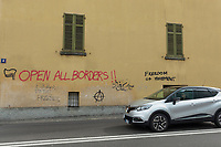 "Switzerland. Canton Ticino. Chiasso. A woman drives a car from Italy. She has just entered into Switzerland. On the wall, a graffiti with the words "" Open all borders"" and ""Freedom of movement"". Due to the Italian government's decision to impose travel restrictions in most of northern Italy over the Covid-19  (also called Coronavirus) outbreak, only Italian citizens with working permits can enter into Switzerland. 9.03.2020 © 2020 Didier Ruef"