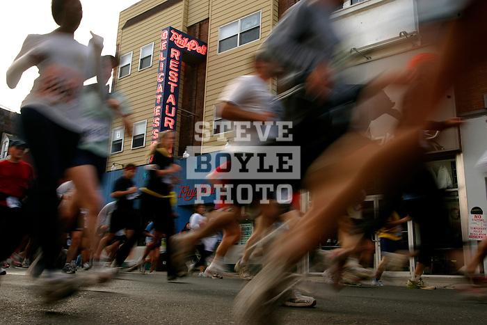Runners pass by Philadeli on South Street during the Philadelphia Marathon in Philadelphia, Pennsylvania on November 19, 2006.