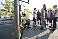 """Nach den pogromartigen Ausschreitungen gegen eine Fluechtlinsunterkunft im saechschen Heidenau am Freitag den 21. August 2015 durch Anwohnerinnen der Ortschaft, kamen am Samstag de 22. August 2015 ca. 250 Menschen in die Ortschaft um ihre Solidaritaet mit den Gefluechteten zu zeigen.<br /> Am Vorabend hatten Rassisten, Nazis und Hooligans sich zum Teil Strassenschlachten mit der Polizei geliefert um zu verhindern, dass Fluechtlinge in einen umgebauten Baumarkt einziehen. Ueber 30 Polizisten wurden dabei verletzt.<br /> Bis in die Abendstunden des 22. August blieb es trotz spuerbarer Anspannung um die Unterkunft ruhig. Im Laufe des Tages wurden immer wieder Gefluechtete mit Reisebussen gebracht was von den wartenenden Heidenauern mit Buh-Rufen begleitet wurde. Vereinzelt wurde auch """"Sieg Heil"""" gerufen, was die Polizei jedoch nicht verfolgte.<br /> Kurz vor 23 Uhr griffen Nazis und Hooligans dann wie am Vorabend die Polizei mit Steinen, Flaschen, Feuerwerkskoerpern und Baustellenmaterial an. Die Polizei mussten mehrfach den Rueckzug antreten, scheuchte den Mob dann von der Fluechtlingsunterkunft weg. Dabei wurden auch wieder Traenengasgranaten verschossen. Mindestens ein Nazi wurde festgenommen.<br /> Im Bild: Gefluechtete vor dem Zaun, der den ehemaligen Baumarkt umgibt.<br /> 22.8.2015, Heidenau<br /> Copyright: Christian-Ditsch.de<br /> [Inhaltsveraendernde Manipulation des Fotos nur nach ausdruecklicher Genehmigung des Fotografen. Vereinbarungen ueber Abtretung von Persoenlichkeitsrechten/Model Release der abgebildeten Person/Personen liegen nicht vor. NO MODEL RELEASE! Nur fuer Redaktionelle Zwecke. Don't publish without copyright Christian-Ditsch.de, Veroeffentlichung nur mit Fotografennennung, sowie gegen Honorar, MwSt. und Beleg. Konto: I N G - D i B a, IBAN DE58500105175400192269, BIC INGDDEFFXXX, Kontakt: post@christian-ditsch.de<br /> Bei der Bearbeitung der Dateiinformationen darf die Urheberkennzeichnung in den EXIF- und IPTC-Daten nicht entfernt werden, """
