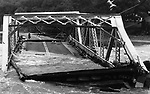 The iron bridge over across the Shepaug River in Washington Depot dropped into the current after high waters ate away the abutments.