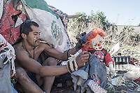 A deported man who lives stuck in a tent in the Canal, El Bordo. His doll represents his family. Tijuana, Mexico. Jan 05, 2015.