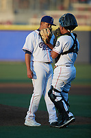Kannapolis Cannon Ballers catcher Victor Torres (2) visits with relief pitcher Angel Acevedo (30) during the game against the Columbia Fireflies at Atrium Health Ballpark on May 21, 2021 in Kannapolis, North Carolina. (Brian Westerholt/Four Seam Images)