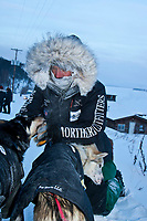 Sven Haltman gives his lead dogs a pet as he takes off their booties shortly after arriving at the village checkpoint of Ruby during the 2010 Iditarod