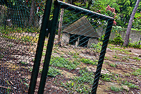 An open gate to the abandoned pit at the Havana Zoo, Havana, Cuba, 12 February 2011. The largest and the oldest zoo in Cuba (founded in 1939) is located in a centric neighborhood of the capital. Since the 1990s Cuba struggles with chronic economic crisis and therefore the strong marks of rundown and lack of sources are evident within the whole zoological garden. A lot of cages are empty and out of use for long time, the remaining animals are captured in poorly maintained pits. Concrete enclosures have no vegetation, all facilities are unkept. The food supply is often inadequate and visitors throw junkfood to the animals because there are no zookeepers around.