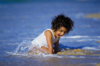 A small girl plays at shoreline of a beach on the north shore of Oahu.