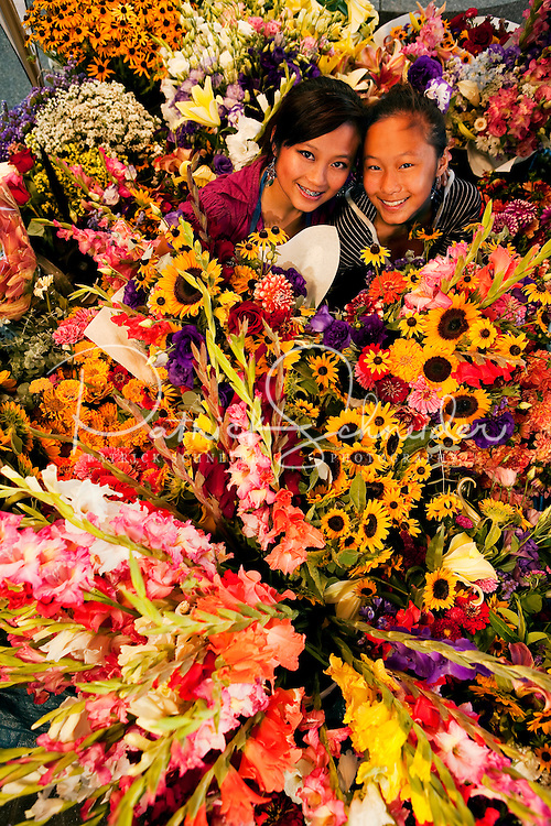 Two sisters operate their family's flower stand in downtown Charlotte, NC. The family grows flowers on their North Carolina farm, then sells the fresh-cut flowers in bulk, as mixed-flower bouquets and as skillfully designed impromptu flower arrangements from under a tent on Tryon Street, a few blocks south of Charlotte's Square in the heart of downtown Charlotte. The florists operate their farmers-market-type flower stand most weekdays during the summer, serving customers who work in uptown Charlotte. In addition to offering shoppers good deals on fresh cut flowers, the flower growers are a bright oasis on Charlotte's city streets.