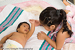 newborn baby girl one month old  Mexican American prerereaching interaction with older sister, age 3 horizontal
