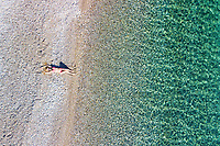 A beautiful woman at the beach Agios Dimitrios of Alonissos island from drone view, Greece