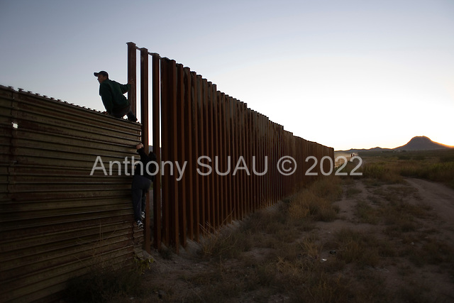 Agua Prieta, Mexico.October 22, 2006..A young Mexican man and woman jump over the border fence to enter the city of Douglas in the USA illegally in the very early morning hours..