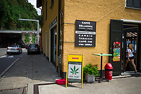 Switzerland. Canton Ticino. Gandria. Border control at Dogana Gandria. The Caffe Bellarma is the last cafe and shop before the Italian border. An outside billboard advertises the sale of products from the Edel Hemp Switzerland SA , a company which sells online and through vending machines products made from hemp, cannabis CBD, hemp flowers and its derivatives. A green cannabis leaf is used as marketing tool on a poster laid on the sidewalk. In the background, a swiss customs officer controls the cars leaving Switzerland.  The business of selling cannabis CBD is registered with the Swiss Federal Health Office. The Swiss legal requirements have a 1 percent THC limit compare to the European Union (EU) where the THC limit is limited to 0.3 percent. Cannabidiol (CBD) is a phytocannabinoid discovered in 1940. It is one of some 113 identified cannabinoids in cannabis plants and accounts for up to 40% of the plant's extract. Cannabidiol can be taken into the body in multiple ways, including by inhalation of cannabis smoke or vapor, as an aerosol spray into the cheek, and by mouth. It may be supplied as CBD oil containing only CBD as the active ingredient (no included tetrahydrocannabinol [THC] or terpenes), a full-plant CBD-dominant hemp extract oil, capsules, dried cannabis, or as a prescription liquid solution. 27.07.2019 © 2019 Didier Ruef
