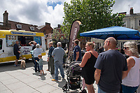 BNPS.co.uk (01202) 558833<br /> Pic: Zachary Culpin/BNPS<br /> <br /> Pictured: People queueing up for free ice-creams which were handed out in Wimborne town square to mark the occasion.<br /> <br /> A much-loved ice cream seller was given a fitting send off by colleagues who followed his funeral cortege in a convoy of 10 ice cream vans. <br /> <br /> John Lennie spent over 40 years selling ice creams from his trusty van in his local community.<br /> <br /> So dedicated was he to his job that he was still doing his rounds just two days before he died at the age of 79.<br /> <br /> His daughter, Jemma Lennie, led the procession in her father's old colourful truck at his funeral in Wimborne, Dorset.