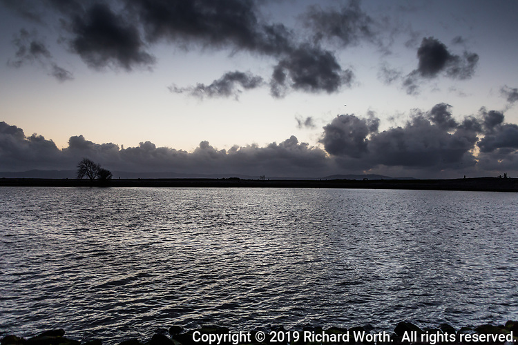 Evening at water's edge with clouds on the horizon and floating over the rippled waters of the small boat lagoon at the San Leandro Marina Park on San Frnacisco Bay.