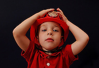 A young boy shows off his red firefighter hat.