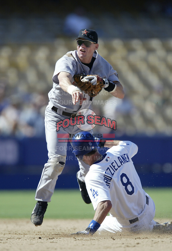 Craig Biggio of the Houston Astros throws to first base after forcing out Mark Grudzielanek of the Los Angeles Dodgers at second base during a 2002 MLB season game at Dodger Stadium, in Los Angeles, California. (Larry Goren/Four Seam Images)