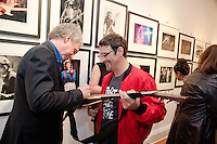 "Bob Gruen signs a guitar for a guest at the Bob Gruen ""Rock Seen"" photo exhibition at Art629 in New York City. May 4, 2012. © Kristen Driscoll/MediaPunch Inc."