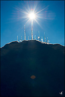 Upside-down icicles on snow in the morning, with sun star effect (sunburst).  The icicles resemble a strange icy cityscape of skyscrapers.