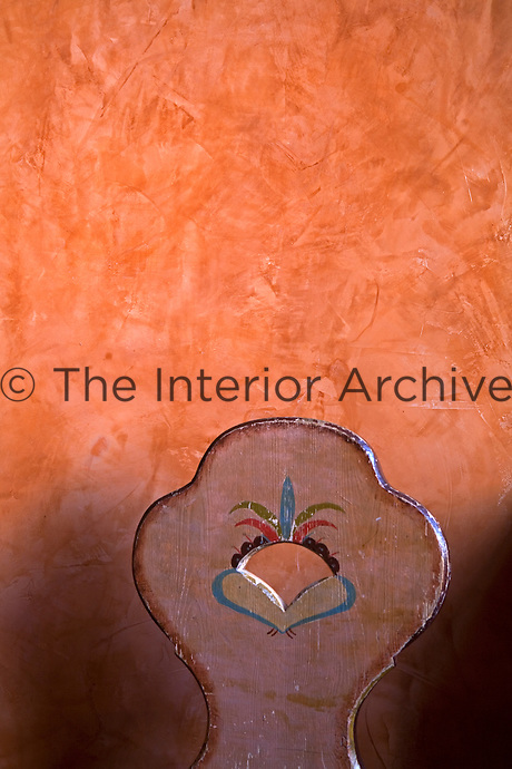 Detail of a hand-painted wooden chair back against a terracotta colour wall