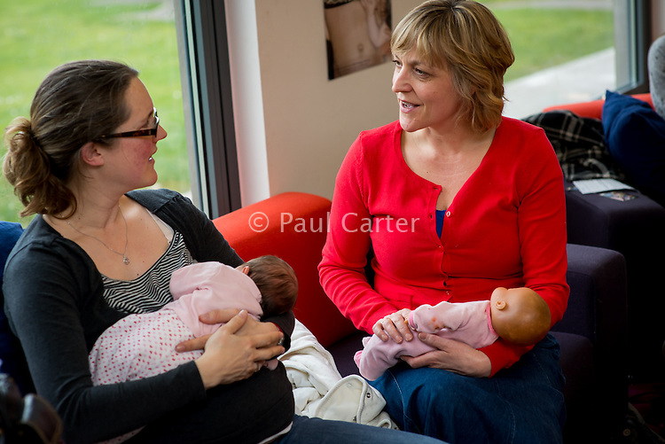 """A midwife, using a doll to demonstrate, discusses breastfeeding techniques with a young woman at a drop-in breastfeeding support centre.<br /> <br /> Image from the breastfeeding collection of the """"We Do It In Public"""" documentary photography picture library project: <br />  www.breastfeedinginpublic.co.uk<br /> <br /> Hampshire, England, UK<br /> 13/03/2013<br /> <br /> © Paul Carter / wdiip.co.uk"""