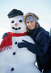 Deutschland, Bayern, Chiemgau: junge Frau umarmt laechelnd einen Schneemann   Germany, Bavaria, Chiemgau region: young woman smiling, embraces a snowman