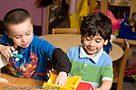 Education Preschool 3-4 year olds two boys playing with people figures and vehicles horizontal