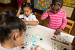 Education Preschool 3-4 year olds group of girls playing poistion recognition bingo placing cards on boards