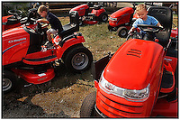 Two young boys try out riding lawn mowers, which were on display at a county fair.  Model released image can be used to illustrate many purposes.