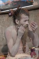 Pashupatinath, Nepal.  Sadhu (Holy Man) at Nepal's Holiest Hindu Temple Views Himself in Mirror Prior to Painting his Face.