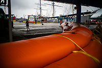 "NEW YORK, NY - AUGUST 4: People walk next to water barriers used to prevent flooding at the South Street Seaport as city gets ready for tropical storm Isaias on August 4, 2020 in New York City. The Tri-State area ""New York, New Jersey and Connecticut"" is preparing for torrential rain, strong winds from Tropical storm Isaias. (Photo by Eduardo MunozAlvarez/VIEWpress)"