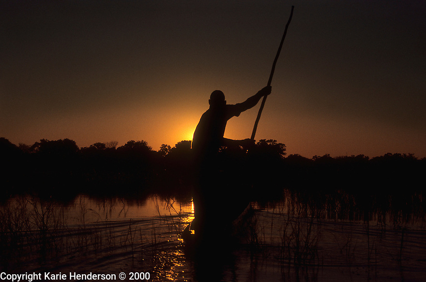 """""""Electricity"""", a guide in the Okavango Delta, Botswana steers a mokoro, dugout boat, into the sunset. Photo by, Karie Henderson © 2000"""