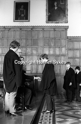 """Threepenny Day. February 27th. Eton near Windsor Berkshire, England 1975.<br /> <br /> In 1514 Mr Robert Rede of Burnham near Eton left in his Will a sum of money that gave each boy in College 2d to attend his obit service and annual requiem.  He stipulated that his and his wife's memory shall be """"recalled yearly, while the world shall endure."""" Provost Lupton left in his Will dated 1535 a further 1d for a like purpose and to help improve the boys food. In Lupton's Will he also bequest a further 2s 8d, to succeeding Provosts, other members of staff received 1s 4d and less depending on status.  The scholars still received the 1d in a threepenny piece, the other 2d being from the gift of Provost Bost who succeeded Lupton.<br /> <br /> Lupton was an English ecclesiastic, lawyer-cleric, chaplain to Henry VII and Henry VIII and Provost of Eton from 1502-1535. (The chairman of Eton's governing body.) The annual Threepenny Day distribution takes place after lunch in the College Hall on the anniversary of his death. <br /> <br /> After lunch starting with the lowest boy, there are seventy Collegers, known as Kings Scholars, these are boys who have passed the College Election examination and have been awarded a scholarship line up to receive a threepenny piece. Kings Scholars are distinguished by their black gowns, and have the initials KS attached to their surname on all school lists.  The other boys at the school, more than 1200 of them, are known as Oppidans. They dine in the College Hall alone, and play the winter term wall game for five years, whereas Oppidans play usually, only for one year.  <br /> <br /> With the introduction of decimal coinage in 1972, and the abolition of the threepenny piece. Provost Caccia bought up large stocks of redundant coins to ensure continuation of this custom. The Captain of the School is entitled to any threepenny pieces left over owing to absentees. <br /> <br /> The Captain of School, Provost Harold Caccia, The College Butler with tray"""