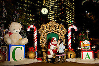 Children sitting on Santa's lap tell their holiday gift hopes to Santa during a holiday celebration in downtown / uptown / center city Charlotte. Photo taken as part of a series of images that capture holiday decorations and festivities in and around Charlotte by Charlotte photographer Patrick Schneider.