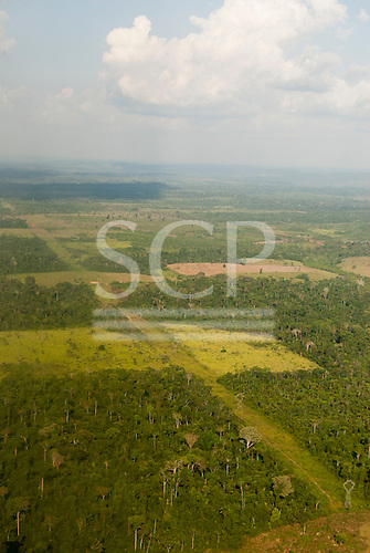 Para State, Brazil. Aerial view showing the advance of deforestation for farming and ranching, with a broad linear clearing for electric power lines through the forest and a patchwork of deforestation.