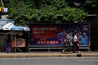 2 men in traditional clothing walk beside an ORODOO mobile phone network advertising, <br /> Yangon on a sunny day of July 2017