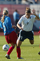 Mia Hamm goes airborne over the leg of Russia's Vera Stroukova. The USWNT defeated Russia 5-1 on  September 29, at Mitchel Athletic Complex, Uniondale, NY.