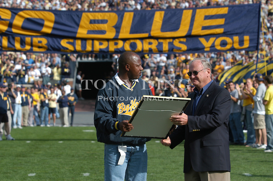 Former Michigan football player Anthony Carter receives the Football Hall of Fame award from his head coach Bo Schlembechler at the Michigan-Penn State game in Michigan Stadium on Saturday, October 12, 2002 (Tony Ding/Daily).