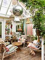 Rusting garden chairs with a variety of striped ticking cushions furnish the small conservatory which features a number of different pendant lights and a glittering disco ball