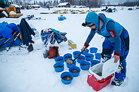Anja Radano portions her dogs' food into bowls in the morning at the Nikolai checkpoint during the 2018 Iditarod race on Wednesday March 07, 2018. <br /> <br /> Photo by Jeff Schultz/SchultzPhoto.com  (C) 2018  ALL RIGHTS RESERVED