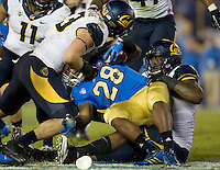 California defenders tackle Malcolm Jones of UCLA during the game at Rose Bowl in Pasadena, California on October 12th, 2013.   UCLA defeated California, 37-10.
