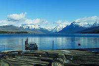 Lake McDonald on a fall morning. Snow capped mountain with drifting clouds surround the lake. Glacier National Park