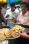 Office workers having meal during break at  a street food stall in Dalhousie area of Kolkata. Street food stalls are serving the office goers for decades. All kind of Indian foods are available on the street at an affordable price. They sale them openly. Street food stalls are another results of unempoloyment and over poppulation. They serve millions of people in India. Kolkata, West Bengal,  India  7/18/2007.  Arindam Mukherjee/Landov