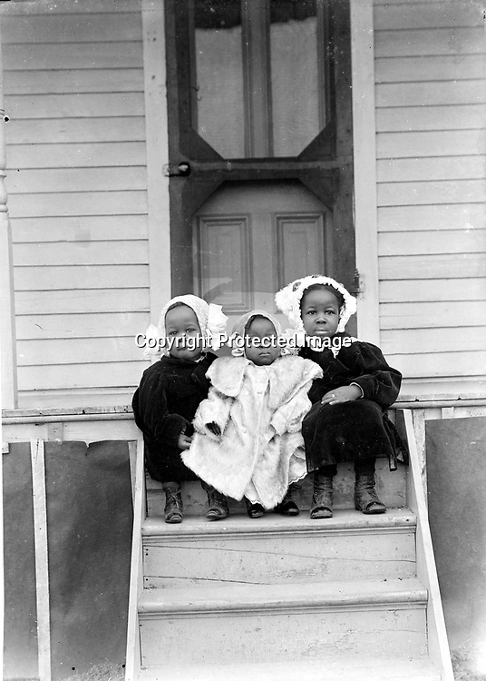 SISTERS AND BROTHERS. The trio crowded on the step is almost certainly two sisters flanking a little brother. The older sister wears a ring.<br /> <br /> Photographs taken on black and white glass negatives by African American photographer(s) John Johnson and Earl McWilliams from 1910 to 1925 in Lincoln, Nebraska. Douglas Keister has 280 5x7 glass negatives taken by these photographers. Larger scans available on request.