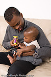5 month old baby boy held by father interested in toy vertical African American